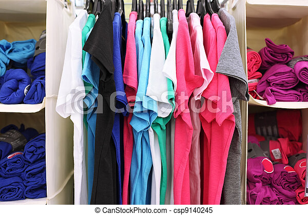Variety of multicolored casual clothes in shop; T-shirts hang on racks and rolled into rolls - csp9140245