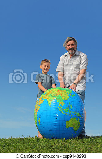 boy and his grandfather standing on lawn near big inflatable globe and smiling - csp9140293