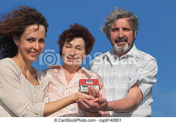 adult daughter and her parents holding house model and smiling, blue sky - csp9140801