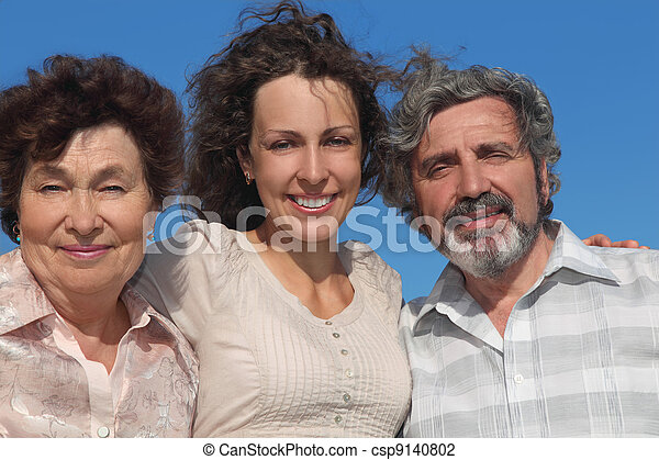 portrait of adult daughter and her parents smiling, blue sky - csp9140802