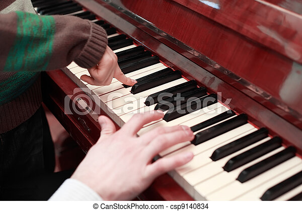 hands of a father and son playing on brown piano, black and white keys - csp9140834