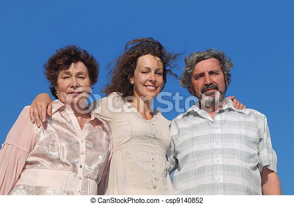 portrait of adult daughter and her parents embracing, blue sky - csp9140852