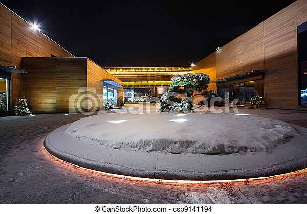 Building of trading complex with flowerbed and fir-tree in center - csp9141194