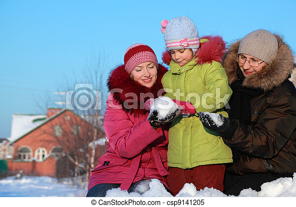 father and mother offer to daughter to make snowball outdoors in winter near house - csp9141205