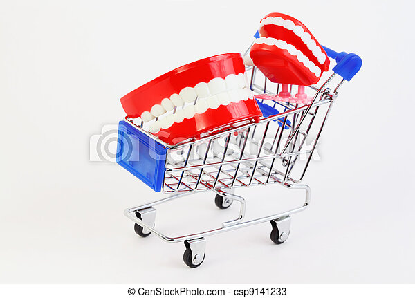two small toys jaw with white teeth in purchasing cart on white background - csp9141233