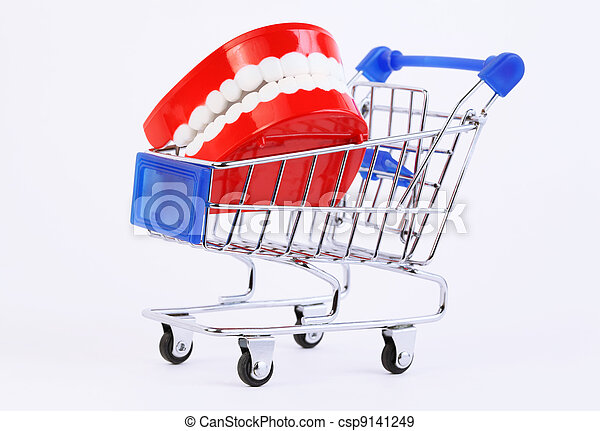 small toy jaw with white teeth in purchasing cart on white background - csp9141249