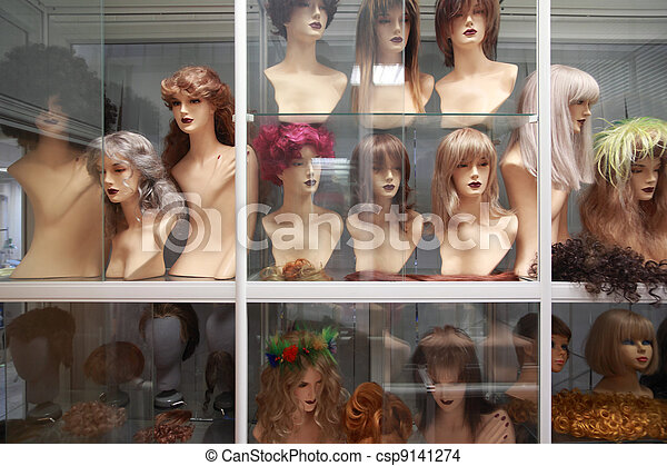 Wigs on mannequins, rows of wigs on white shelves behind glass - csp9141274