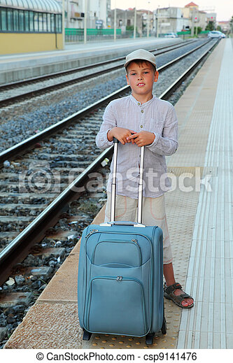 little boy stands on platform of railway with big blue travel bag - csp9141476