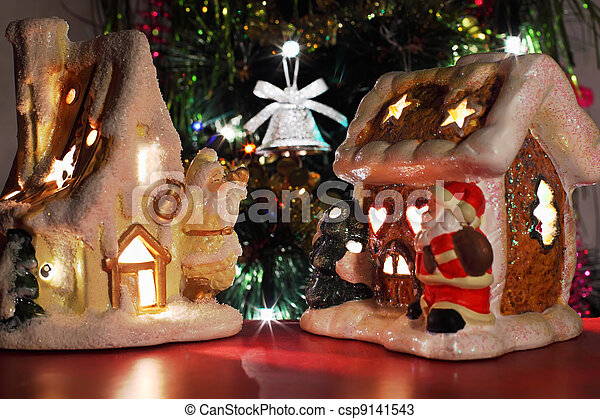 two decorative Christmas toy houses, shiny bell on Christmas tree - csp9141543