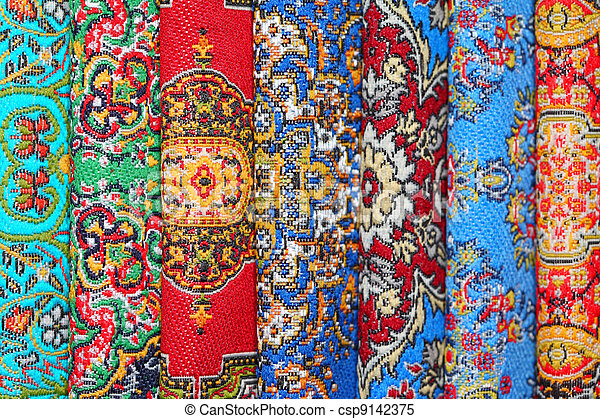 Seven varicoloured carpets lie in rouleau on each other on vertical line - csp9142375