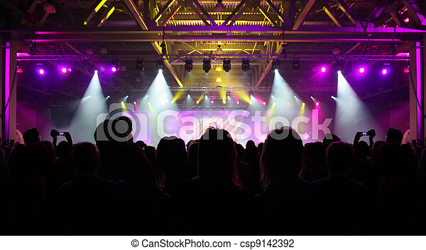 Crowd of spectators having fun at party; backs and silhouettes of people
