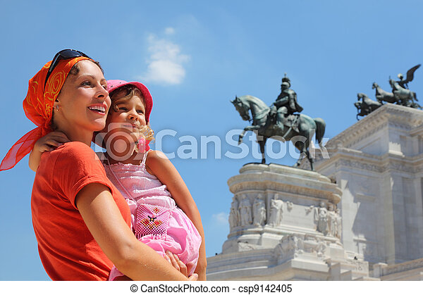 Mother is holding little daughter, equestrian monument to Victor Emmanue II near Altar of fatherland in Rome, Italy - csp9142405