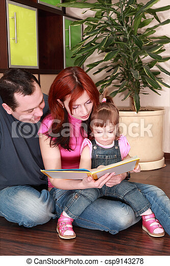 mother, father and little daughter in denim jumpsuit reads book on floor - csp9143278