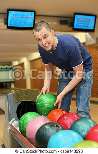 Youth bends over to automat  and takes  ball for playing bowling - csp9143298