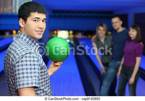 One fellow stands sideways and holds ball for playing in bowling and three friends hearten him, focus on  man - csp9143650
