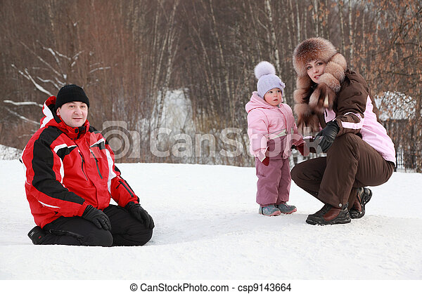 little daughter with mother, father sitting at snow in winter, focus on girl - csp9143664