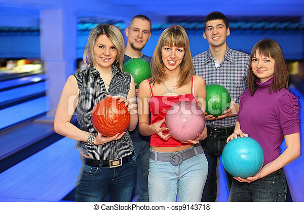 Three girls and two men stand alongside and everybody holds  ball for bowling, focus on girls - csp9143718