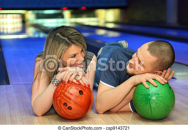 Fellow and girl lie on parquet and look on each other leaning against balls for bowling, focus on girl - csp9143721