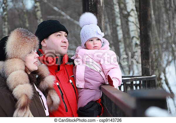 father hugs mother and little daughter looks into distance, winter, focus on girl - csp9143726