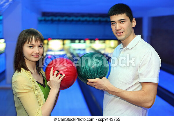 Girl and youth turned  to each other and adjoin balls for bowling - csp9143755