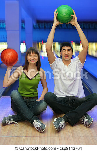 Fellow and girl sit on parquet and lift upwards balls for bowling - csp9143764