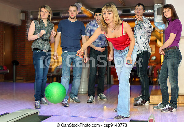 Girl throw ball on lane for bowling and friends worry for result, focus on girl in center - csp9143773