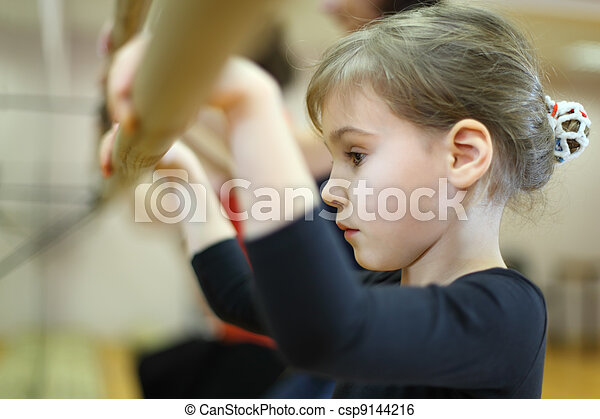 serious face of little girl in ballet class near frame and large mirror - csp9144216