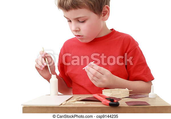 little boy in red T-shirt crafts at small table, boxcutter, glue - csp9144235