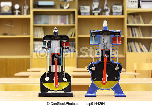 Two models of internal combustion engine on desk in empty physics school class - csp9144264