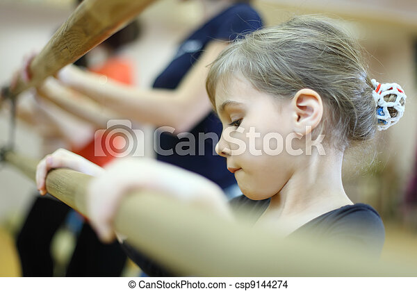 concentrated face of little girl in ballet class near frame and large mirror - csp9144274
