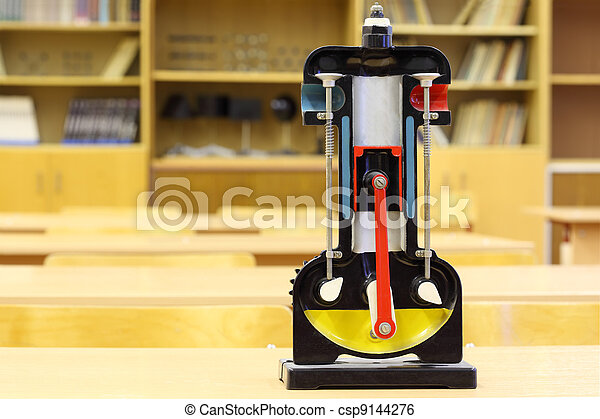 Model of internal combustion engine on desk in empty physics school class - csp9144276