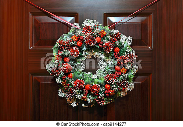 Large artificial circled wreath with knops and bead hangs during Christmas on door