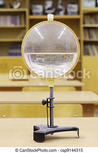 Old water lens for educational experiments in physics; empty school class - csp9144315