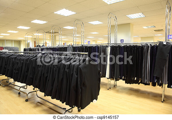 rows of jackets and men trousers on hangers in big light shop - csp9145157