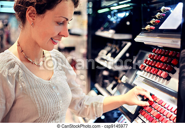 beautiful young woman chooses lipstick in store. bid assortment - csp9145977