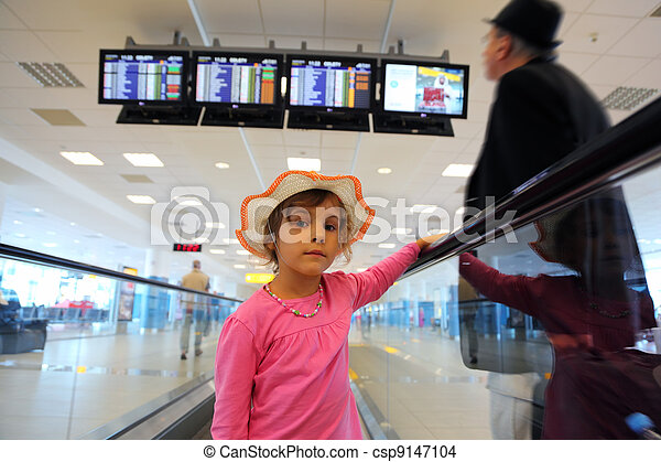 beautiful little girl in hat and pink blouse rides on escalator. old man in black wear. schedule on displays - csp9147104