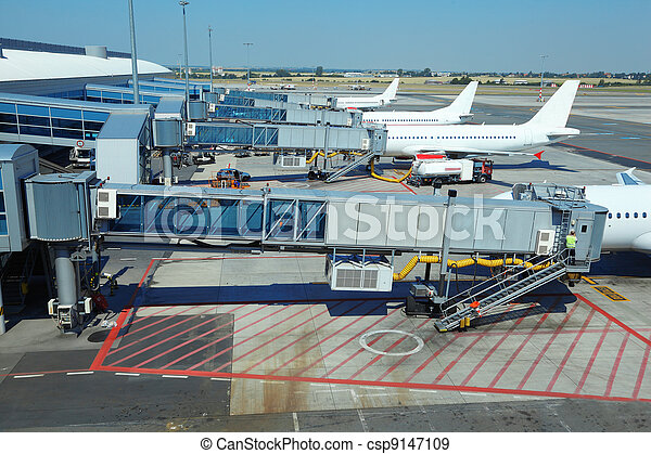 few airliners parked at airport. boarding passengers. service technician - csp9147109