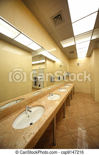 sinks and mirrors in public restrooms, yellow tiles on floor and walls - csp9147216