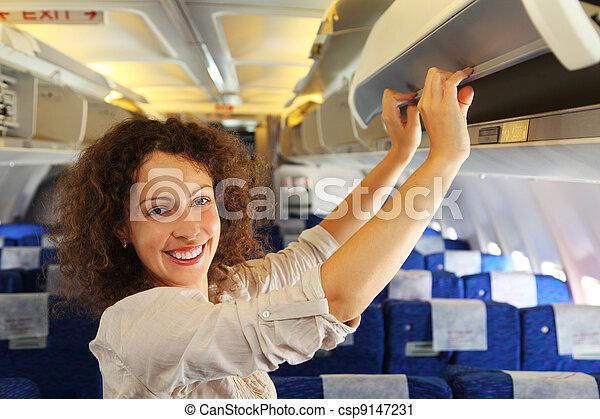 young beautiful woman on airplane adds baggage, rows of blue seats - csp9147231