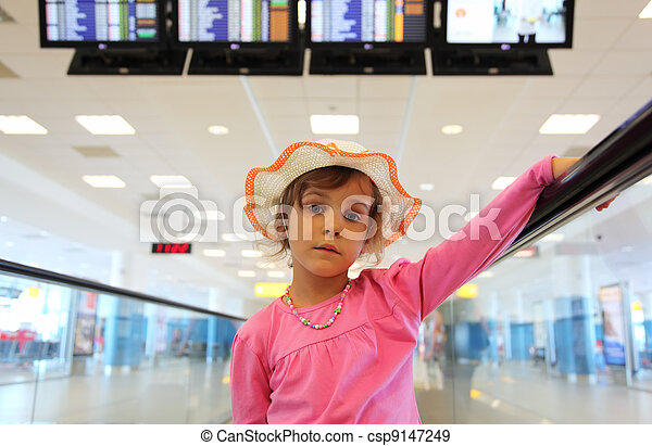 beautiful little girl in hat and pink blouse rides on escalator, schedule on displays - csp9147249