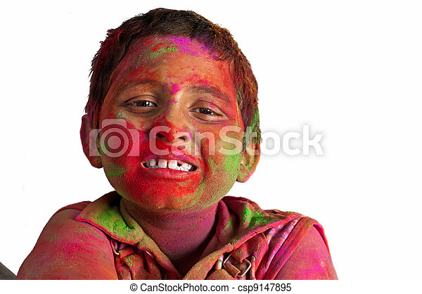 Close up face of young boy playing Holi, smiling with colors on face, Happy Child