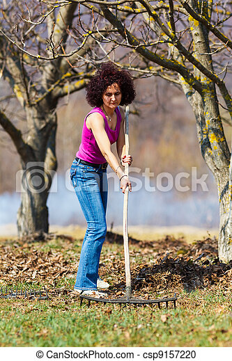 Young woman with a rake in an orchard - csp9157220