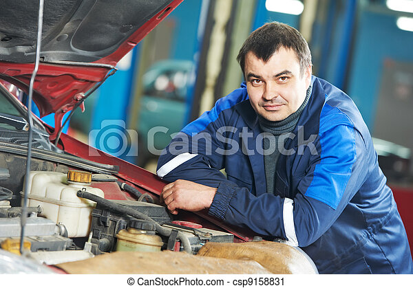 happy mechanic technician at service station - csp9158831