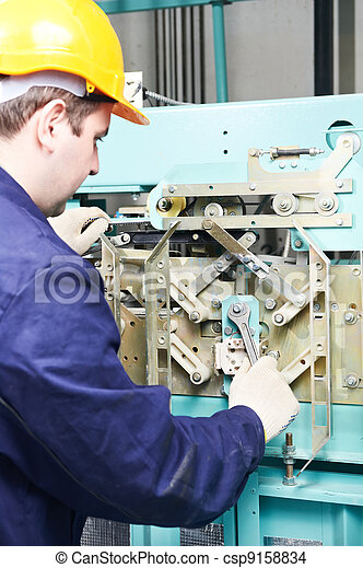 machinist with spanner adjusting lift mechanism - csp9158834