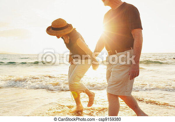 Senior Couple Enjoying Sunset at the Beach - csp9159380
