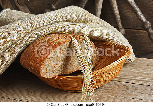slices of rye bread and ears of corn on a wooden table - csp9160894