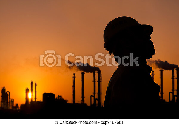 the silhouette of oil refinery worker at sunset - csp9167681