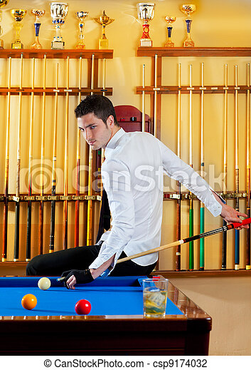 Billiard winner handsome man playing with cue and balls at club - csp9174032