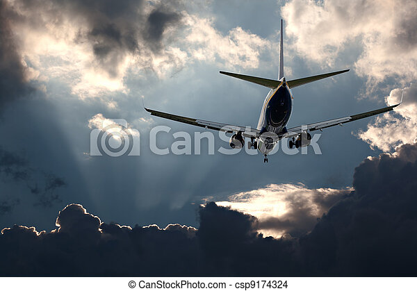 Passenger jet landing against a stormy sky - csp9174324