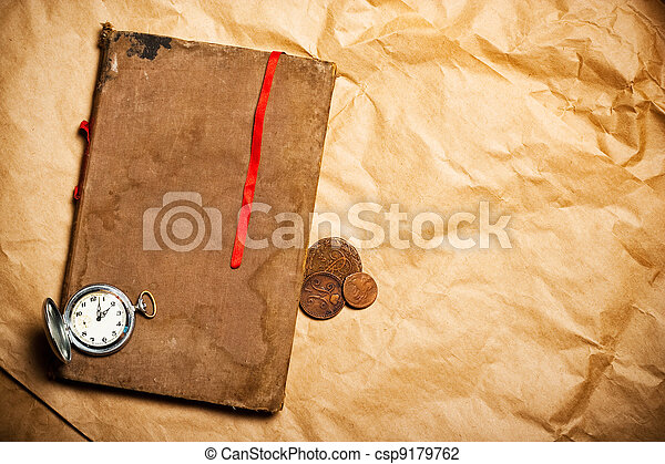 old book with red bookmark and antique watch and coins on yellow paper - csp9179762